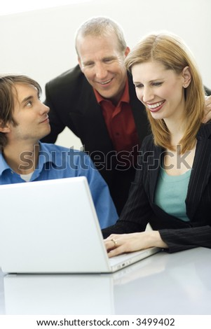 Three workers talk while using a laptop - stock photo