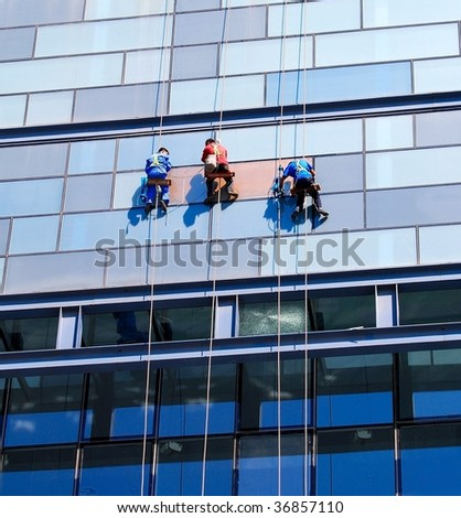 Three workers wash a wall of the skyscraper