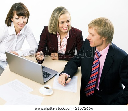 Three working businesspeople sitting at the table - stock photo