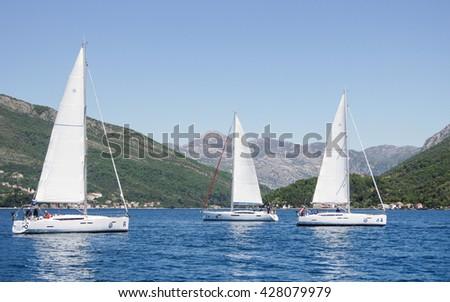 "Three yachts on the water. Tivat, Montenegro - 24 April, 2016 Regatta ""Russian stream"" in God-Katorskaya bay of the Adriatic Sea off the coast of Montenegro. - stock photo"