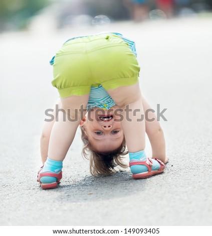 three-year baby girl playing upside down  - stock photo