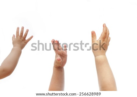 three 1 year old babies raise hands to show their wish isolated on white