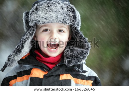 Three year old boy having fun in the outdoor Winter cold and snow - stock photo