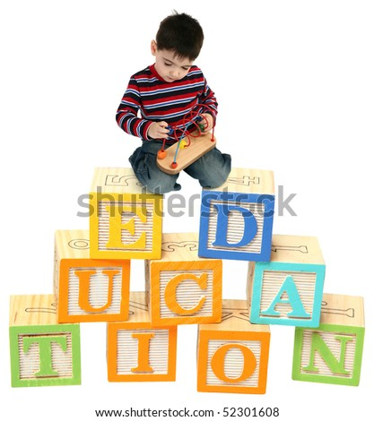 Three year old boy sitting on colorful toy blocks that read EDUCATION.