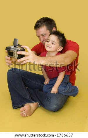 Three year old boy taking family photo with digital camera. - stock photo