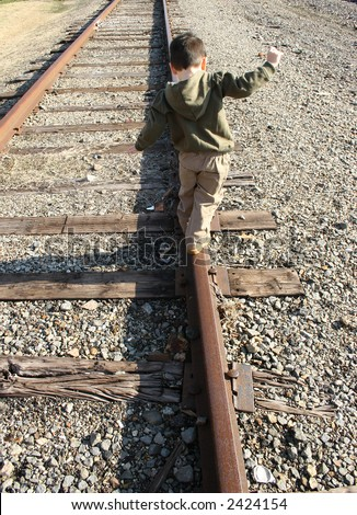 Three year old boy walking the train track. - stock photo