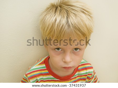 three year old boy with a serious expression against textured wall. - stock photo