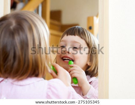 three year old child  painted cosmetics front of  mirror - stock photo