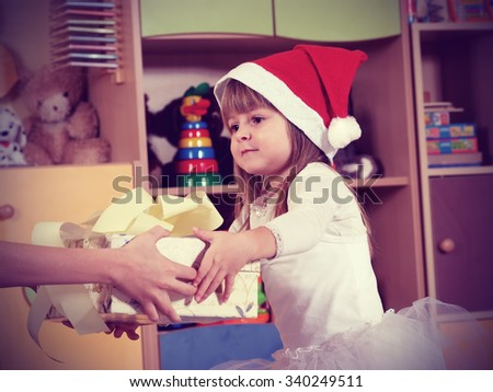 Three year old girl dressed as an angel playing in the nursery vintage  - stock photo