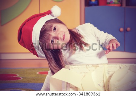 Three year old girl dressed as an angel playing in the nursery vintage