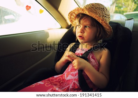 Three year old girl sitting in car seat. - stock photo