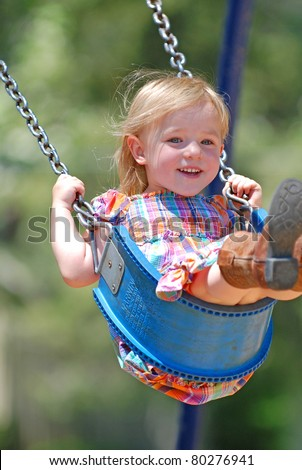 Three year old girl swinging high in a swing smiling. - stock photo