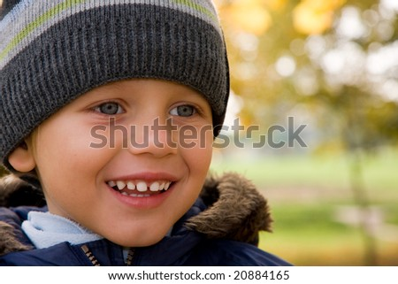 Three years old boy smiling in autumnal scenery - stock photo