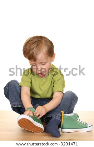 three years old boy tries to put on his sneakers isolated on white - stock photo