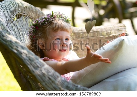 Three years old bridesmaid girl with wreath on the head catching paper hearts - stock photo