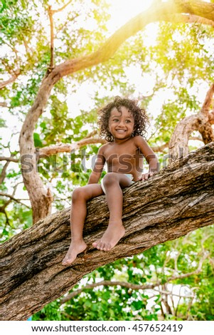 Three years old child sitting on a tree brunch in the jungle forest having fun outdoors
