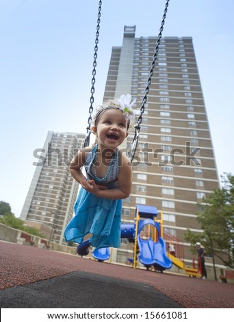 three years -old girl on a swing in the playground - stock photo