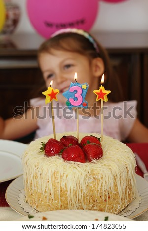 Three years old girl with birthday cake with candles  - stock photo
