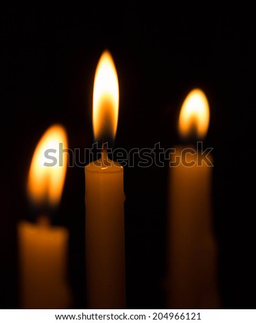 three yellow candles on dark background - stock photo
