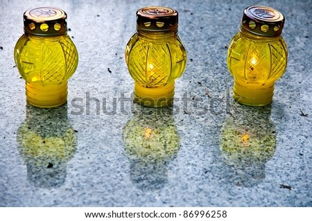 Three yellow candles on grave on the All Saints Day - stock photo