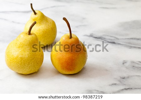 Three yellow pears on a white marble counter top
