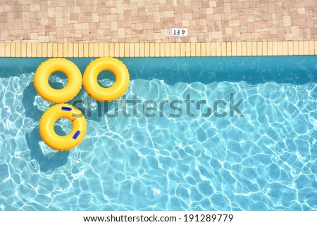 Three yellow pool rings floating in a swimming pool, room for your text - stock photo
