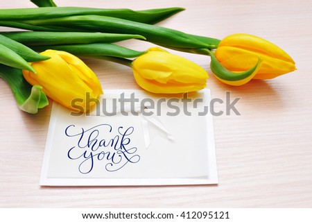 Three yellow tulips with greeting card thank you - stock photo