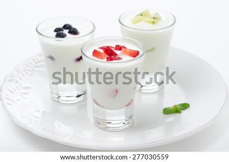 three yogurt with fruit in a glass beaker on a plate horizontal - stock photo