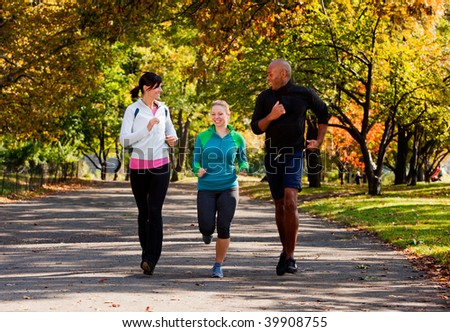Three young adults jogging in the park - stock photo