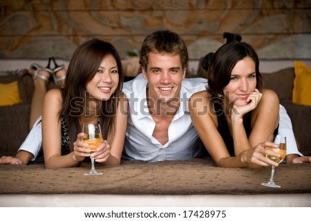 Three young adults lying on a daybed with glasses of wine - stock photo