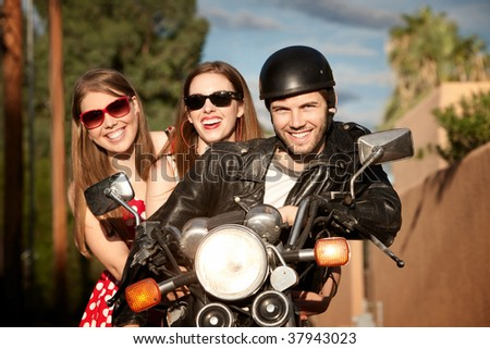 Three young adults posing on vintage motorcycle - stock photo