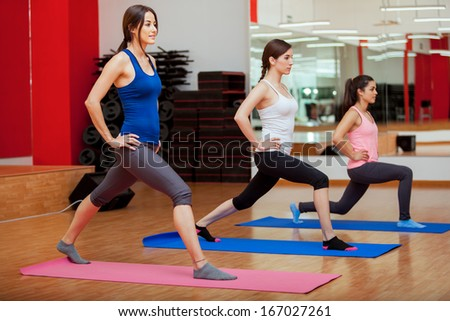 Three young and pretty Latin women doing some cardio and aerobics at a gym - stock photo