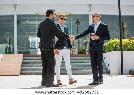 Three young and success arabic businessmen talking outdoor the office, discussing and shaking hands.