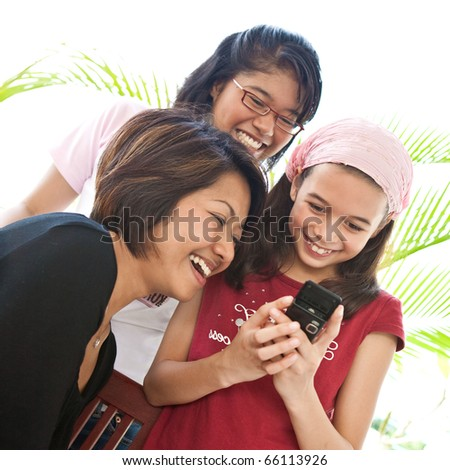 Three young Asian girls sharing a laughter while using a mobile phone - stock photo