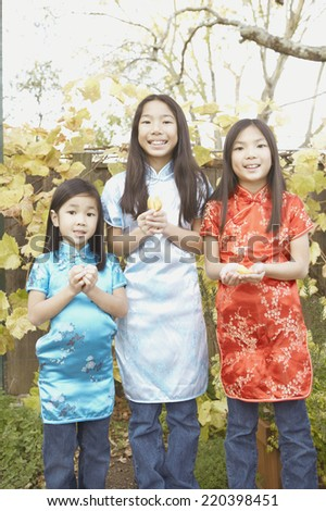 Three young Asian sisters holding fortune cookies - stock photo