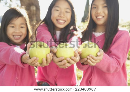 Three young Asian sisters holding green apples - stock photo