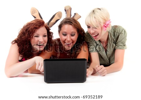 Three young attractive women lying on the floor cross-legged having fun in front the laptop. Studio shot. White background