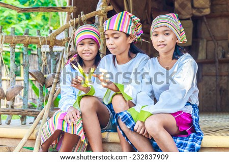 three young beautiful child girls in traditional clothes in bamboo house making toys from palm leaves, Philippines, Malay, Panay