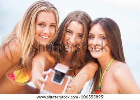 three young beautiful girlfriends having fun on the beach with a vintage camera