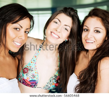 Three young beautiful girlfriends hugging and smiling - stock photo