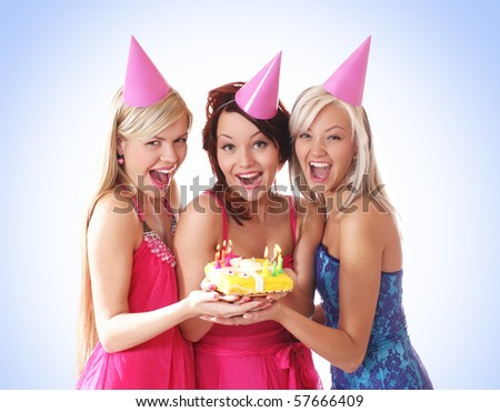 Three young beautiful girls celebrate birthday isolated over white background - stock photo