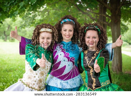 Three young beautiful girls in irish dance dresses showing thumbs up outdoor - stock photo