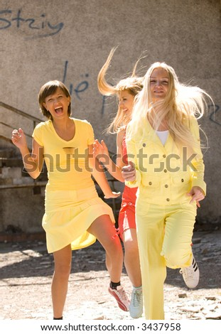 Three young beautiful girls playing and happily laughing - stock photo