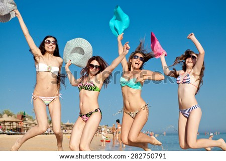 Three young beautiful happy girls in bikinis and colorful hats in their hands are jumping on the beach on vacation - stock photo