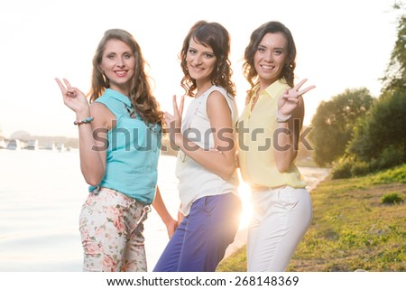 Three young beautiful ladies posing during walk in the city park near bank of the river on a sunset light. - stock photo