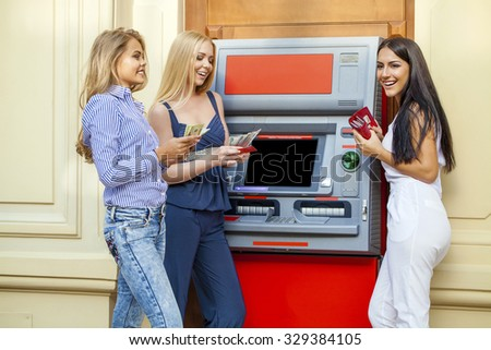 Three young beautiful modern girls using an automated teller machine. ATM, Women withdrawing money or checking account balance - stock photo
