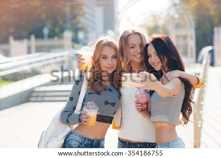 Three young beautiful russin women making self portrait outdoor in the city. Girls making selfie. Friends. Portrait of a three smiling girlfriends making selfie photo on smartphone in the street - stock photo