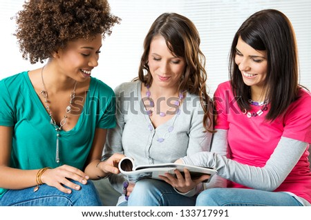 Three Young Beautiful Smiling Women Reading Magazine