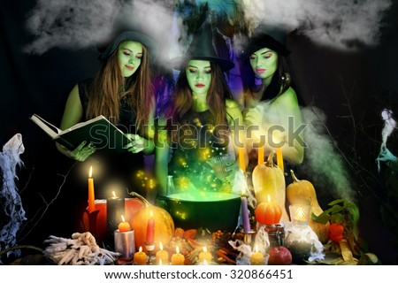 three young beautiful witch in the casserole boiled Seele - stock photo