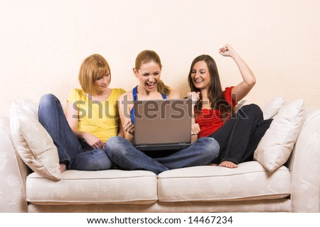 Three young beautiful women are sitting on a lounge with a laptop - stock photo